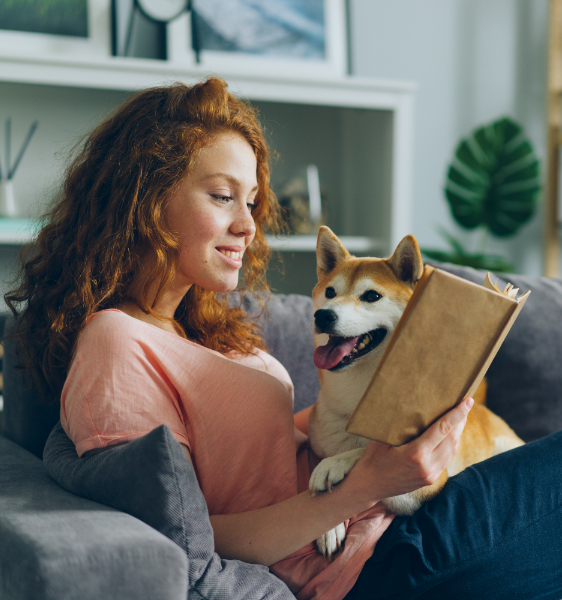 a young woman sitting on her couch, reading a book, with her dog on her lap.
